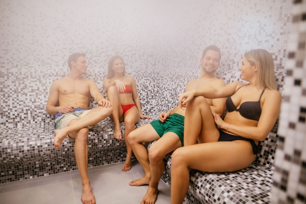 Two young couples relaxing in steam bathroom or sauna